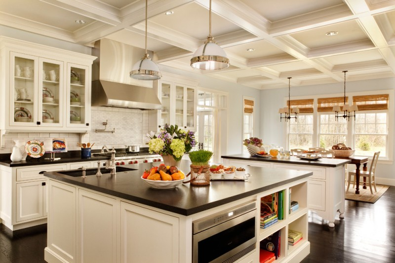 kitchen with coffered ceiling, black granite counter top on cream cabinet for island, cook area, white pendant lamps, wooden dining set