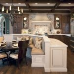 Kitchen With Cream Banquette Area, Cream Counter Top, Brown Wooden Cabinet, Whtie Grey Mosaic Backsplash And Hood