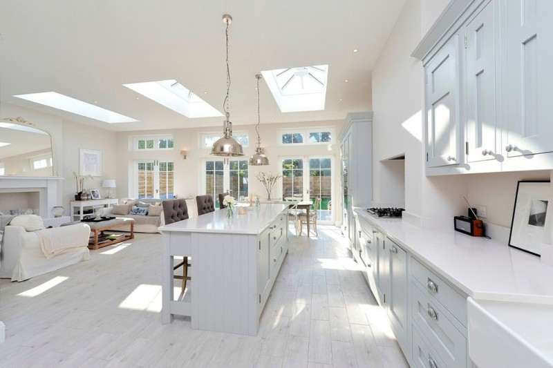kitchen with white cabinet, white countertop, white tainted wooden floor, gold industrial pendant lamp