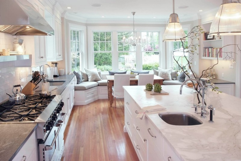 kitchen with white marble counter topo, white tile bakcsplash, white island, white corner seat with grey cuhshion, pendant lamps, chandelier