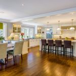 Kitchen With White Oak Flooring, White Island, White Cabinet And Backsplash, Dark Stools, White Book Dining Seat With Green Chushion, Green Lamps, White Pendant Lamps