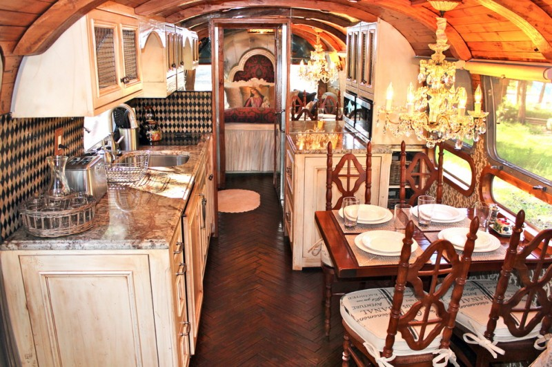 kitchen with wood flooring, brown cabinet, brown marble counter top, cream top cabinet, dark brown table set, black white mosaic tiles backsplash, chendelier