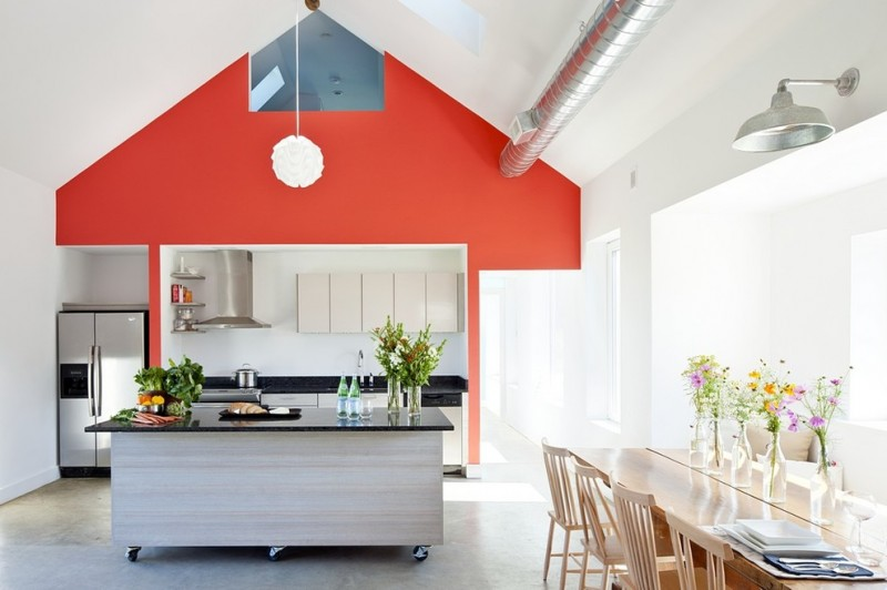 large kitchen with grey island with black countertop, black countertop on the cook, white wall, orange wall on the vaulted ceiling, white nude dining area