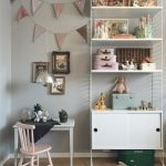 Light Grey Painted Walls With Decorative Triangle Strings White Storage System For Kids' Animal Stuffs Small White Table And Pink Chair Medium Toned Wood Floors