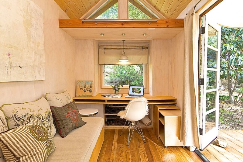 living room in a house trailer with bench with brown cushion, brown wooden table and chair, big window and door