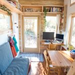 Living Room In A House Trailer With Blue Sofa, Wooden Table And Chairs, Wooden Shelves