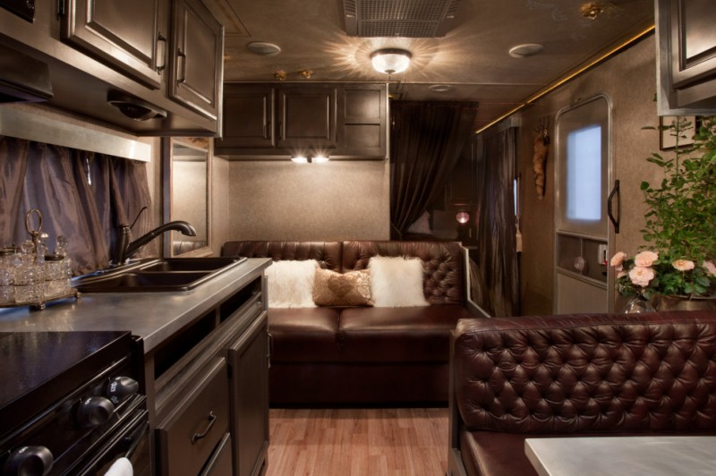 living room in a trailer with wooden flooring, brown leather tufted couch, sink, cabinet, stove, yellow lamp, brown wallpaper