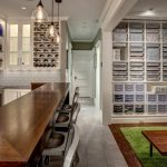 Long And Large Bar With Lear Glass Shelves For Liquor Bottle, Wooden Counter Bar, White Tiles Backsplash, Clear Glass Pendant, Next To Toys Area