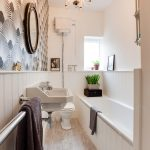 Long Bthroom With Long Small Bathtub, Wooden Flooring, White Sin, Chandelier, White Wainscot, Brown Wallpaper