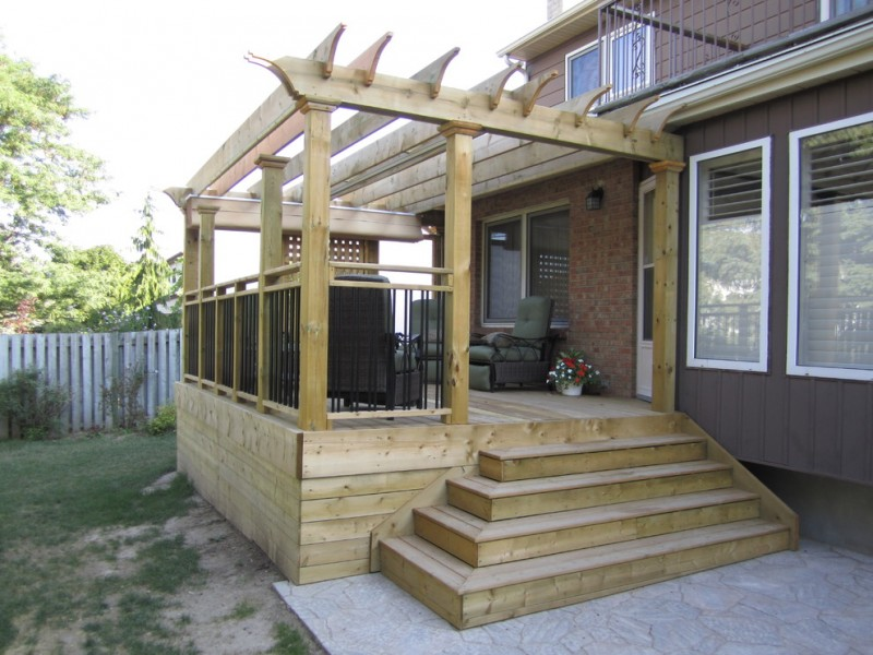 low level deck with white cedar skirting black wrought iron railings with white cedar rail posts