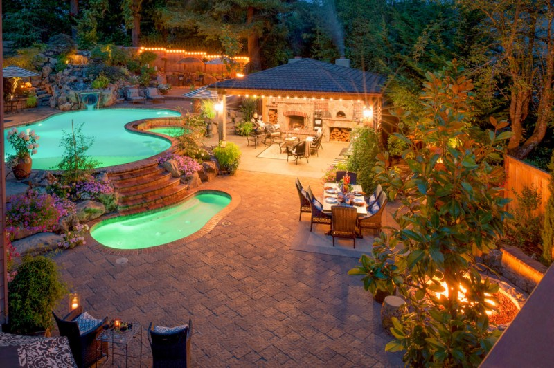 mediterranean landscape wit two pools, plants, lightings under the plants, outdoor dining area, gazebo with dining table set, fireplace, plants