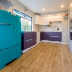 Mid Century Kitchen Design Purple Lower Cabinets White Upper Cabinets White Backsplash Bright Blue Refrigerator Stainless Steel Appliances Wooden Floors