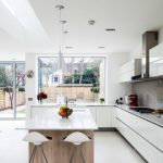Modern Kitchen With White Furniture, White Cabinet With Grey Countertop And Backsplash, White Pendant Lamps, Clear Plastic Chairs