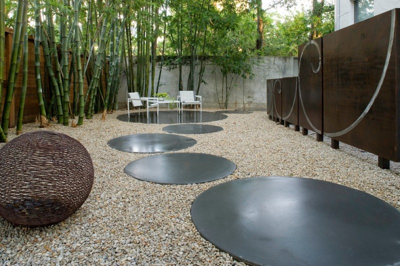 modern landscape with grey concrete path and seating area, wooden screen, timber bamboo, white chairs and table, peebles