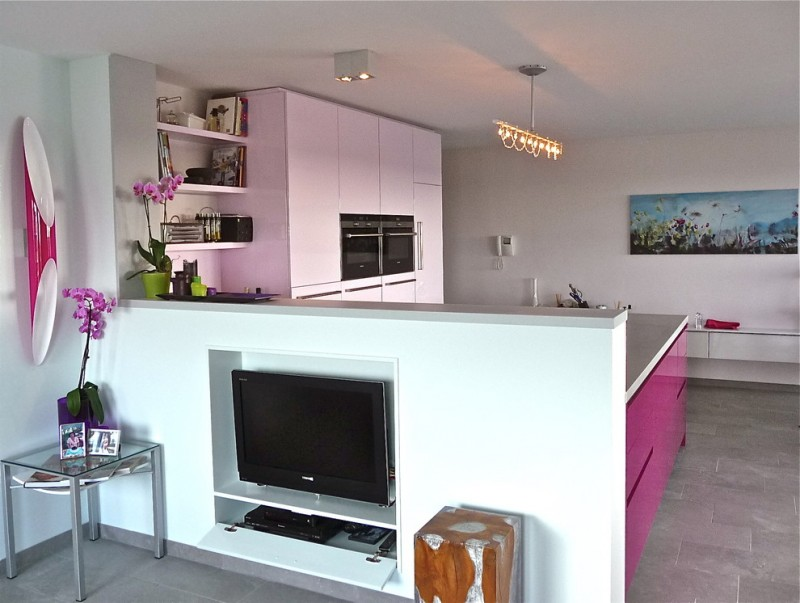 modern minimalist kitchen idea with white flat cabinets stainless steel appliances bright purple kitchen island with white top TV in partition