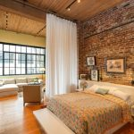 Modern Room With Big Screen And Sofa Brick Wall Bed Pillows Wood Floor Windows Industrial Style Lamp Table
