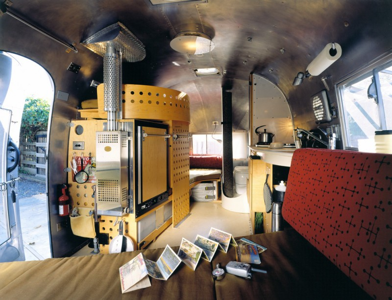 modern trailer interior with chair, sink, small toilet, bed