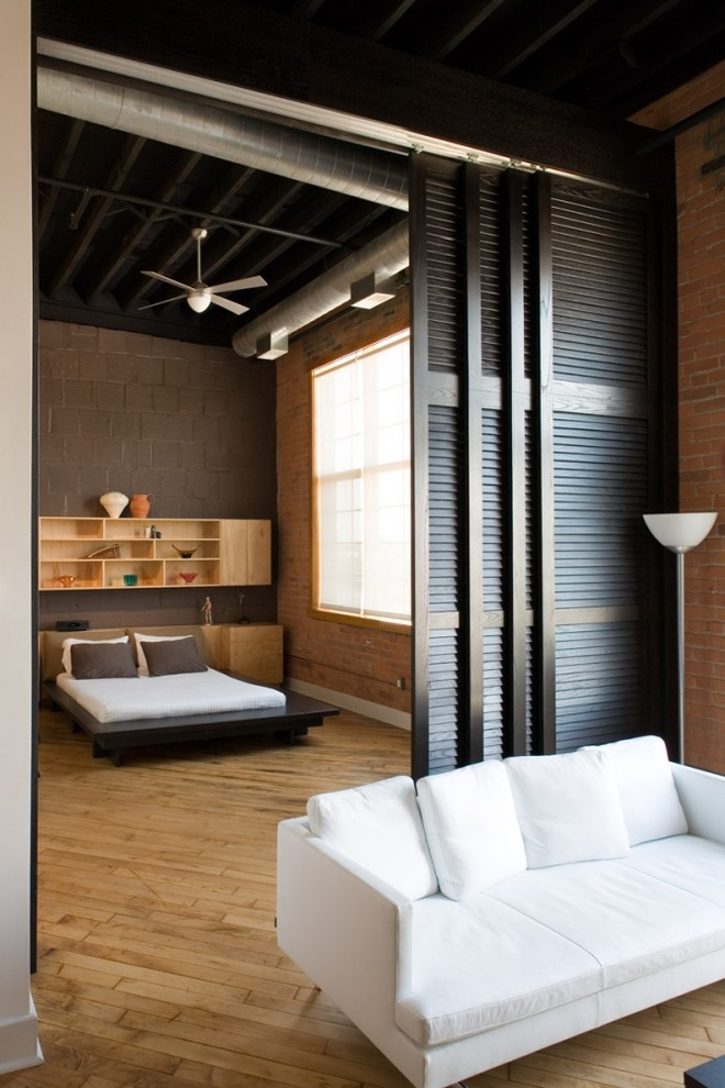 mountain style wood loft bed design hardwood floors wood shelves at the back of bed dark grey brick walls ceiling fan