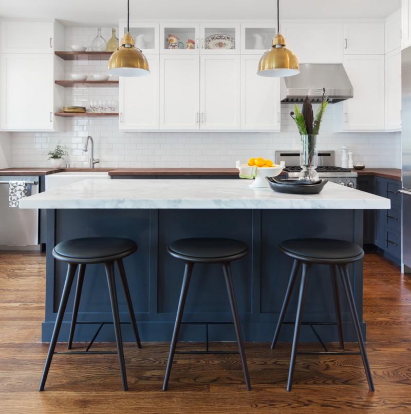 navy blue kitchen cabinet white countertop white raised cabinet white tile backsplash yellow brass hanging lamp dark blue wooden chair