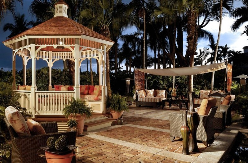 octagon gazebo with white wooden poles and railes, brown roof, vaulted ceiling, wooden deck, built in seating along the rails