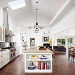 Open Kitchen With Brown Flooring, White Cabinet, Cream Grey Countertop, Stools, Pendants, Wooden Dining Set
