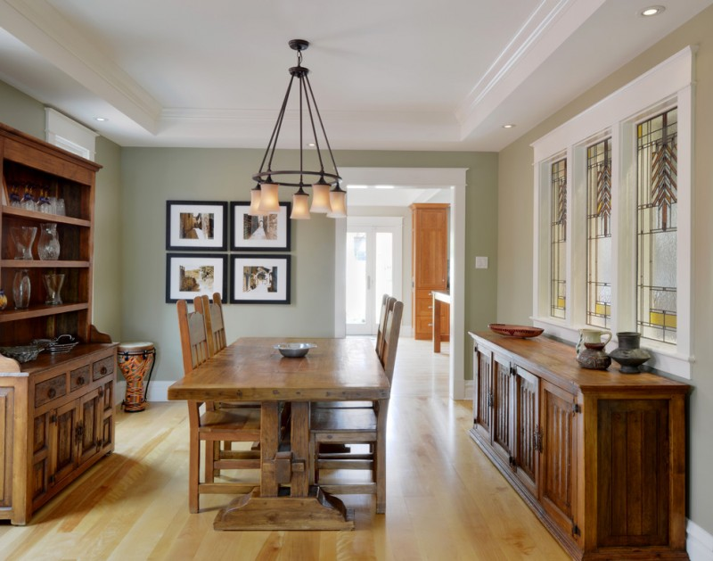 pale toned dining furniture set darker toned buffet and console light toned wood floors light green walls classic hang lamp
