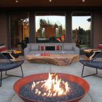Patio With Bronze Bowl Fire Pit, Black Chairs, Grey Sofa, Stone Table