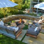 Patio With Fire Pit Built With Boulders And Black Sand, With Bench With Grey Cushion On The Side, Chairs With Grey Cushion, Half Round Built In Seating Area, Umbrella