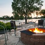 Patio With Fire Pit On Black Cylinder Iron With Grill Put In Round Stones, Chairs Around, Stone Flooring