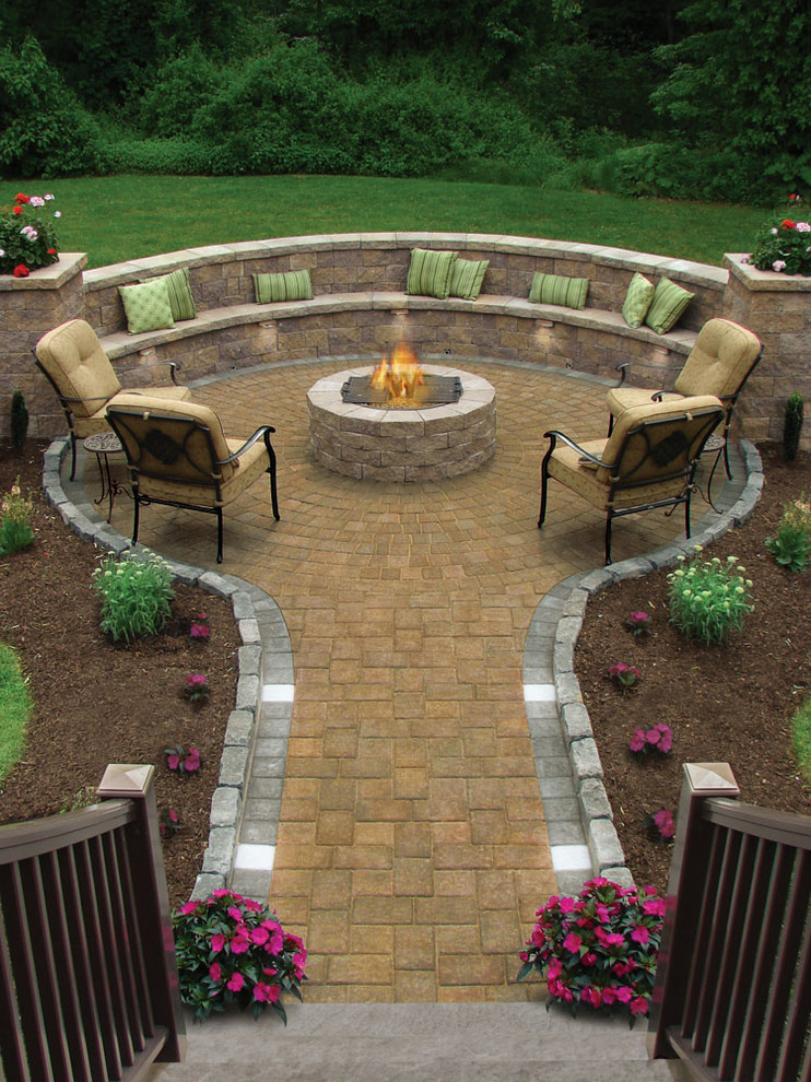 patio with firepits in the middel of round pavers area with built in seating area, chairs, and coffee table