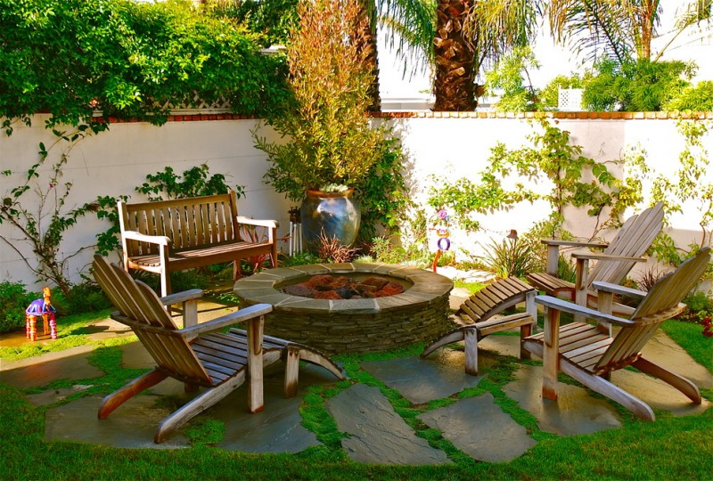 patio with flat stones under the chairs and bench that positioned around a round stone block for fire pit