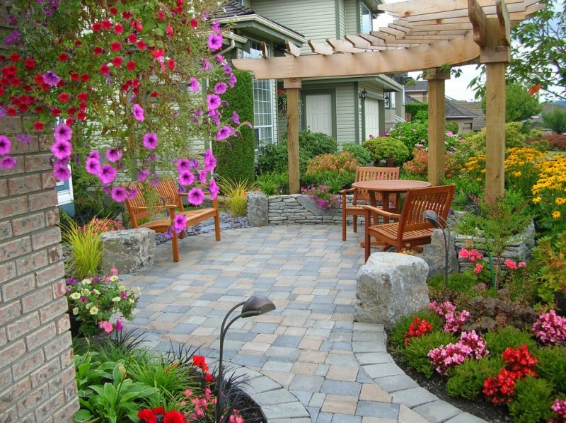 patio with paver in charcoal, neutral, and taupe, and half round wooden pergola, wooden table set, wooden bench, flwers around the patio