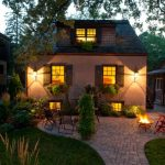 Patio With Pavers, Fire Pit, Chairs Around It, Plants, And Lamps