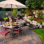 Patio With Pavers, Iron Dining Table Set With Umbrella In The Middle Of The Table, Pool Surrounded By Stones, Plants, Flowers, And Grass