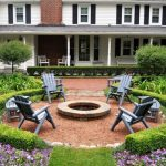 Patio With Round Hedges And Fire Pit In Th Middle Surrounded With Grey Chairs And Bench