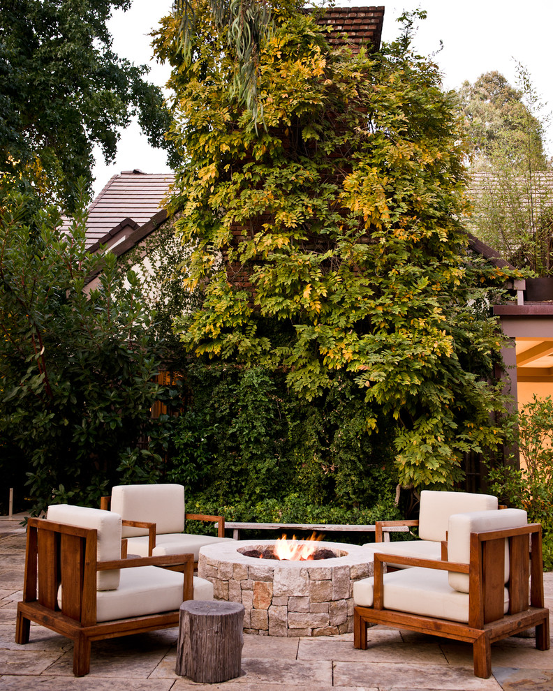 patio with sandstone pavers and fire pit, wooden chair with white cushion