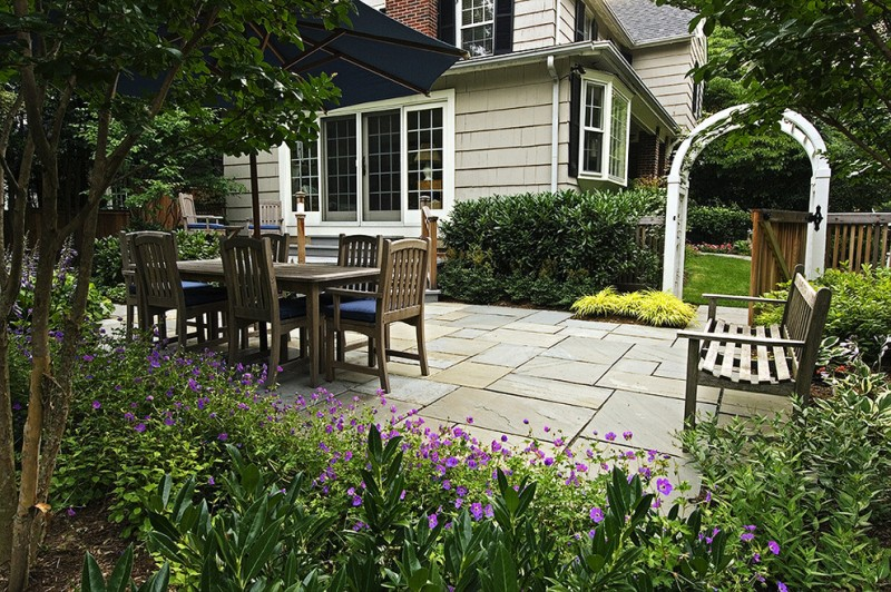 patio with white archway, wooden dining set, wooden bench