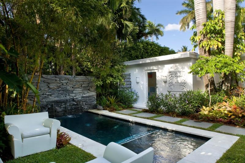 rectangular small pool concrete wall with fountains concrete pavers white concrete sofas
