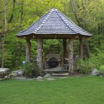 Round Gazebo With Wood Block Poles, Stone Flooring, Chairs, Fire Pit, Shingles Roof