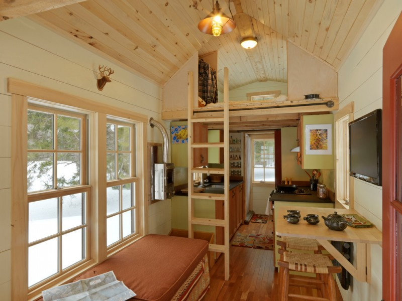 rustic living room in a house trailer with bedroom upstair, kitchen and bathroom in one corner, living room in brown furniture in another corner