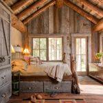rustic mud wood interior bedroom bed pillow carpet door windows logs underbed storage lamps cupboard