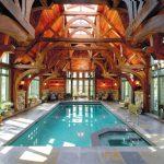 rustic mud wood interior indoor pool big windows pots plants wall lamps seating