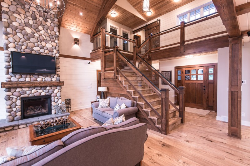 rustic mud wood interior wood floor stone wall wall tv fireplace stairs table sofa pillows wall lamp ceiling lights