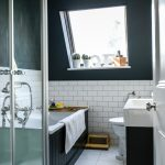 Small Bathroom With Dark Painted Walls To The Ceiling, White Wainscoting, Black Tub With White Inside, Black Cabinet With White Counter Top, White Toilet, Window