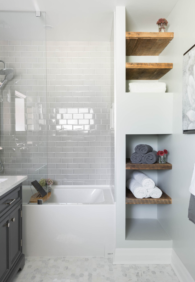 small bathroom with four foot bathtub in white, white tiles on the wall, white tiles flooring, black cabinet with white counter and sink, wooden shelves