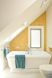 small bathroom with yellow subway tiles wall, mosaic hexagon tiles flooring, white toilet, small white bathtub