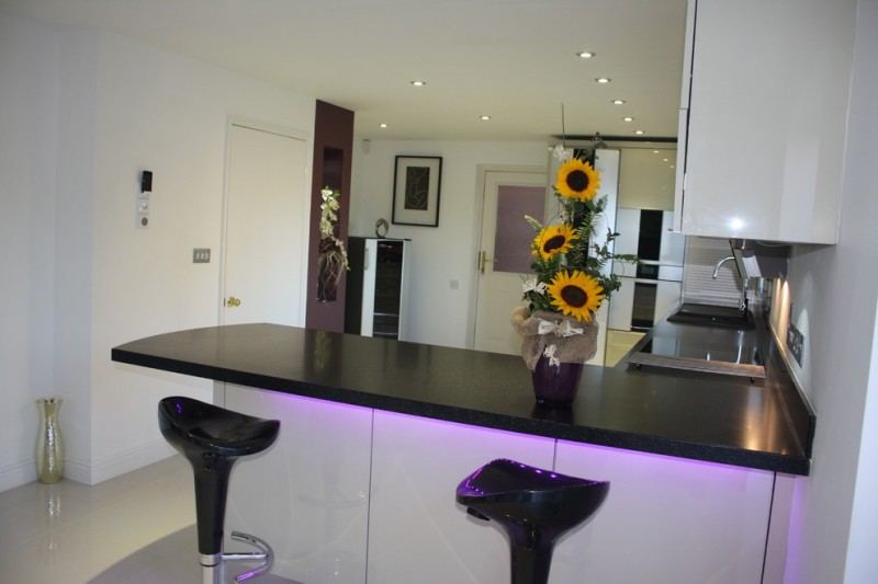 small contemporary kitchen idea with L shape black countertop modern black stools stainless steel appliances white cabinets decorative purple pot for sunflowers