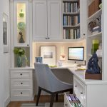 Small Home Office In The Corner With White Wall, White Cabinet And Shelves, Brow Wooden Flooring, Rug, Grey Chair
