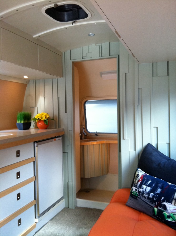 small kitchen in trailer with wooden cabinet, brown counter top, turquoise wall, white ceiling, orange couch, blue pillow