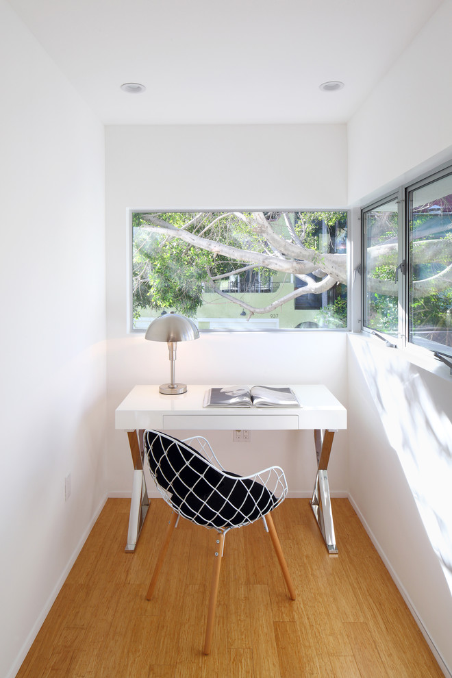 small modern home office with clean white working table with x base white wire working chair with wood base minimalist glass windows oak floors